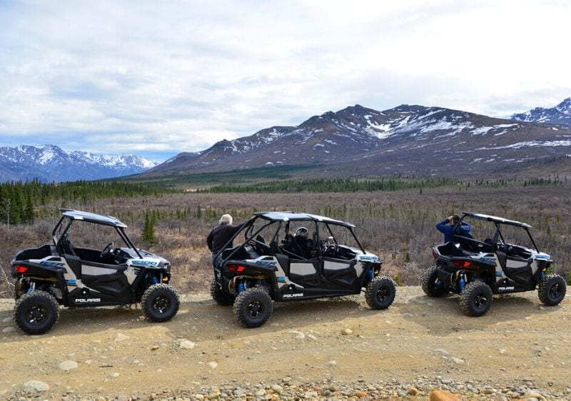 guests and off-road vehicles looking a the scenic mountain range