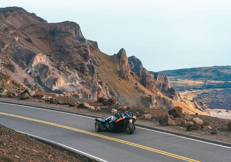 guests driving a Polaris Slingshot along rocky hillside in Hawaii