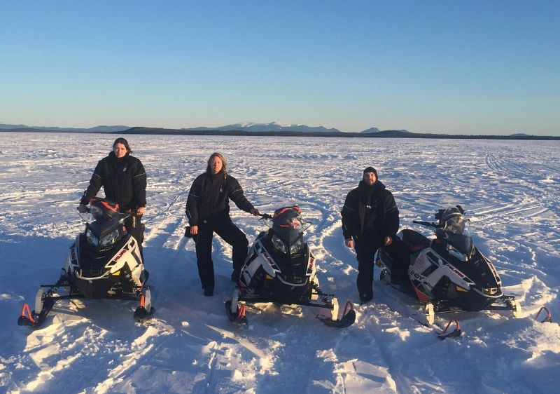 guests-standing-by-Polaris-Snowmobiles-on-a-snow-covered-lake