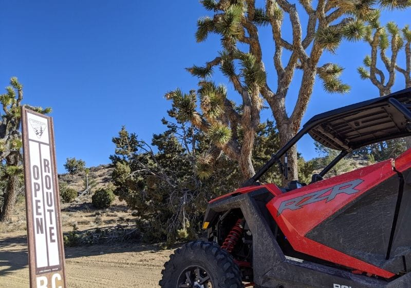 Polaris RZR parked by-an open route sign in the desert