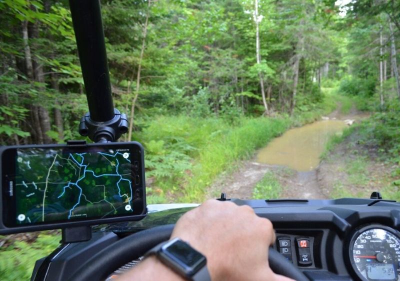 guest-driving-a-Polaris-RZR-on-a-muddy-trail