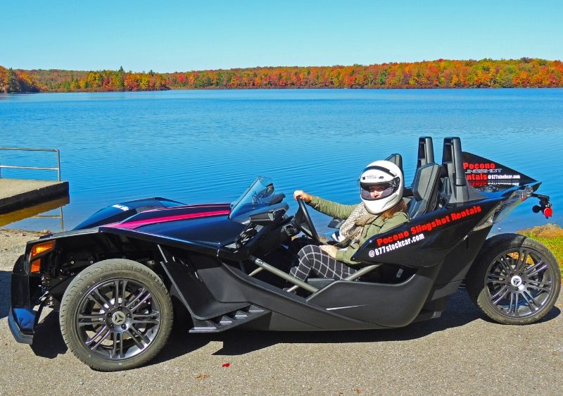 guest-in-a-parked-Polaris-Slingshot-by-the-lake-surrounded-by-fall-colored-trees