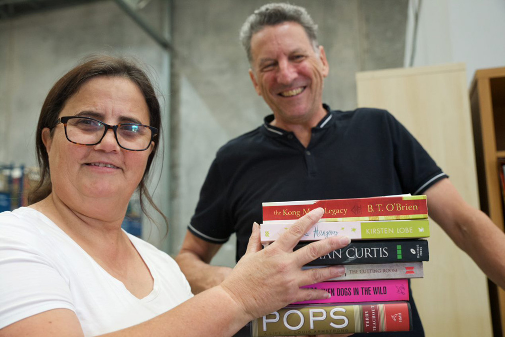 This is a photo of two volunteers sorting books for Brotherhood Books at the warehouse. They are both smiling and happy.
