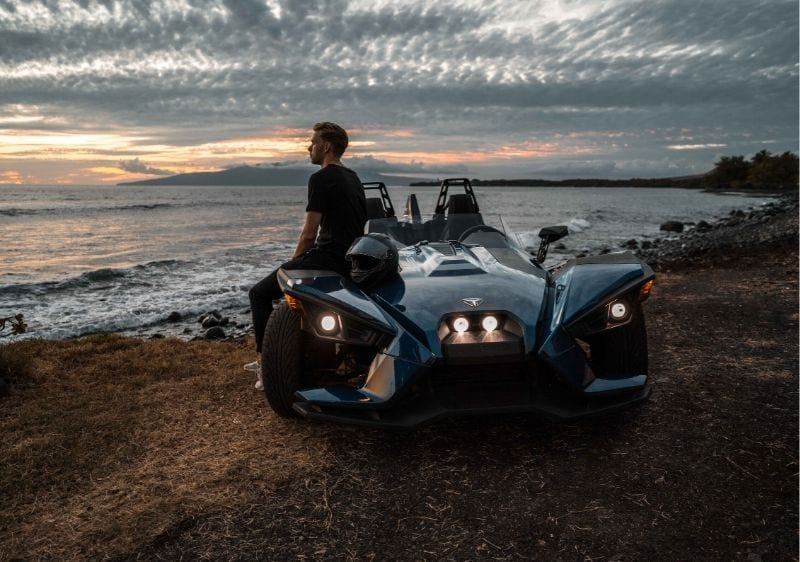 guest leaning on a Polaris Slingshot watching the sunset