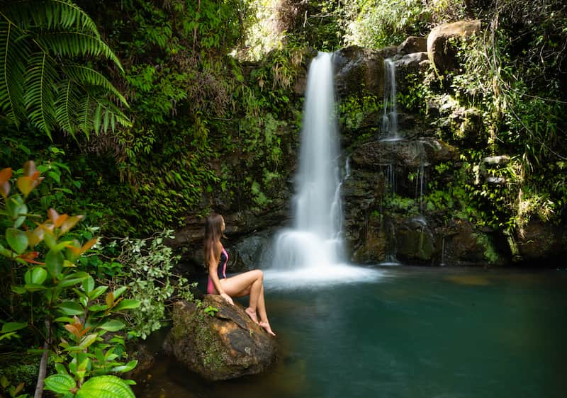 woman-sitting-on-a-rock-next-to-waterfall-in-hawaii