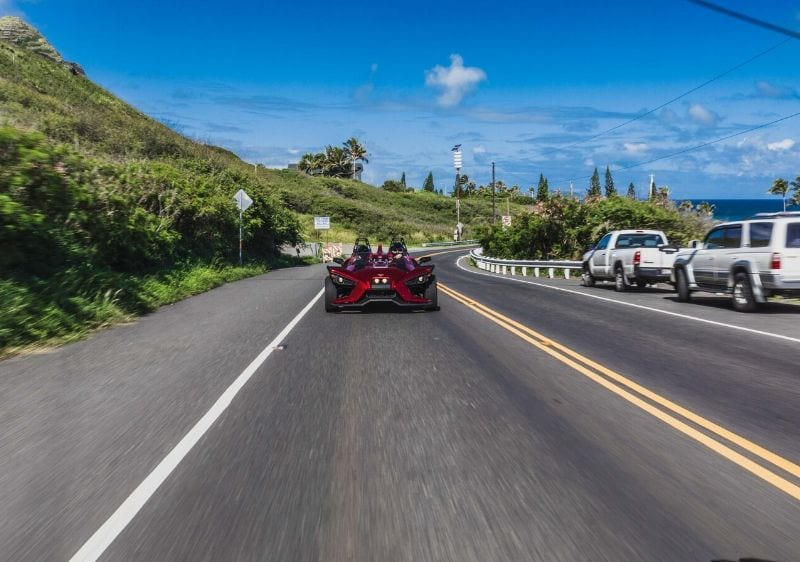 guest driving Polaris Slingshot down a costal highway