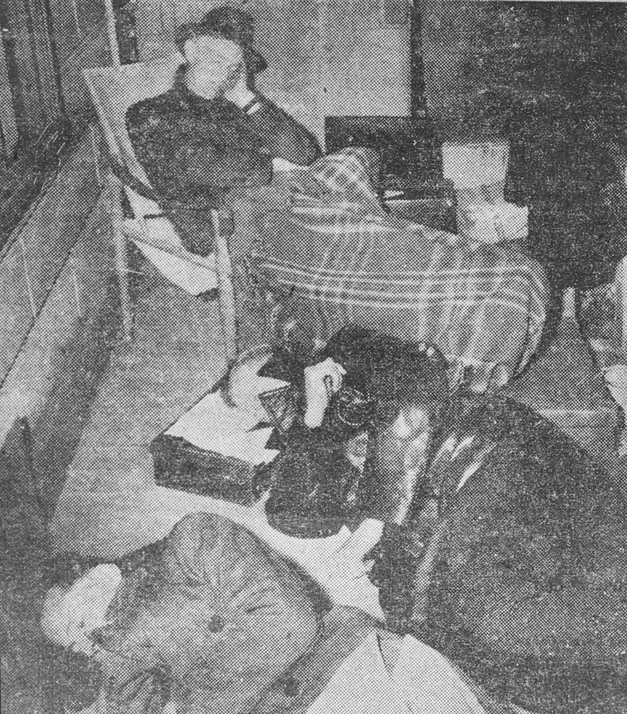 This is a black and white photograph of Father Tucker under a blanket, Frank Coaldrake and Tony Bishop sitting on the verandah of an Armadale house in protest.