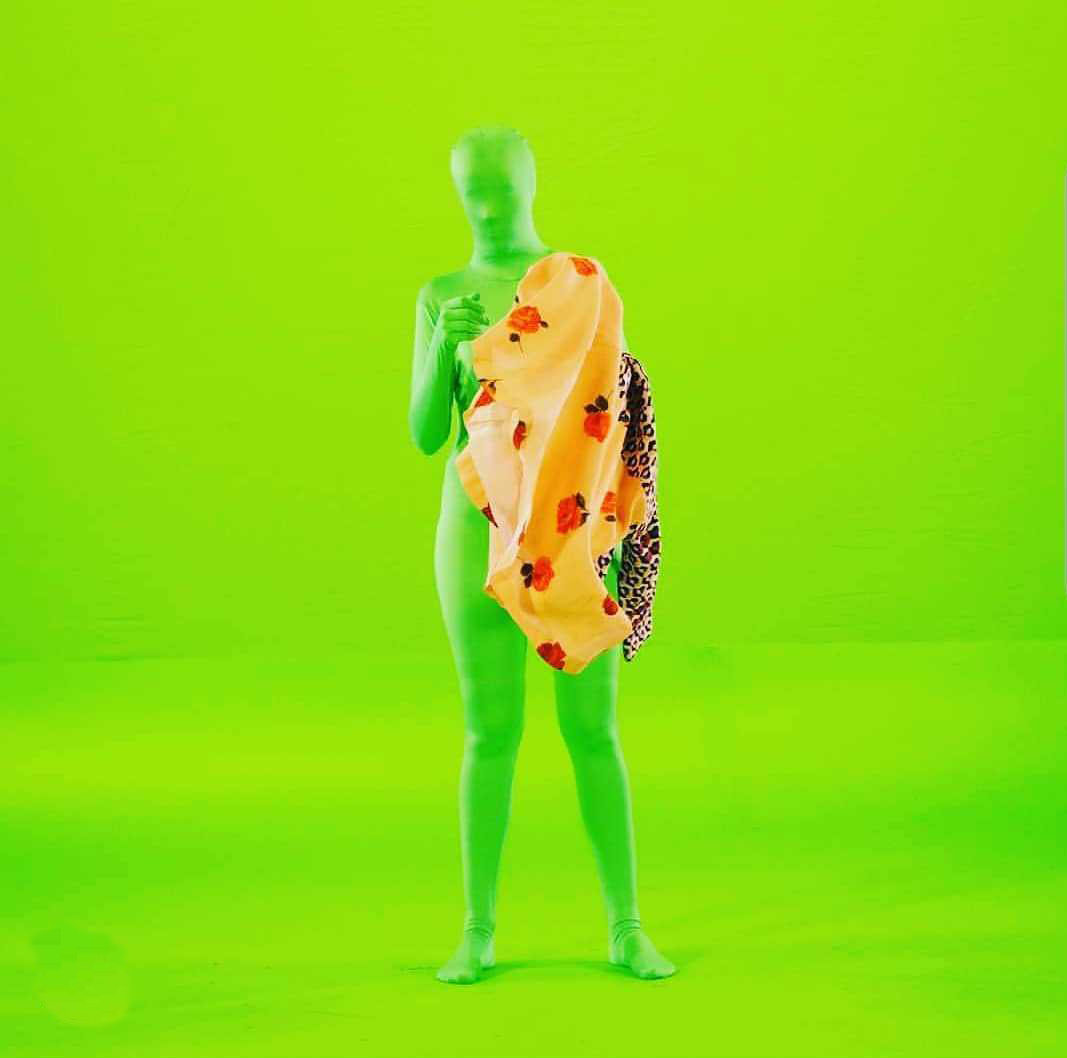 A figure stands in front a bright green screen, wearing a bright green full body suit covering their face. Fabrics are draped over the left side of the body.