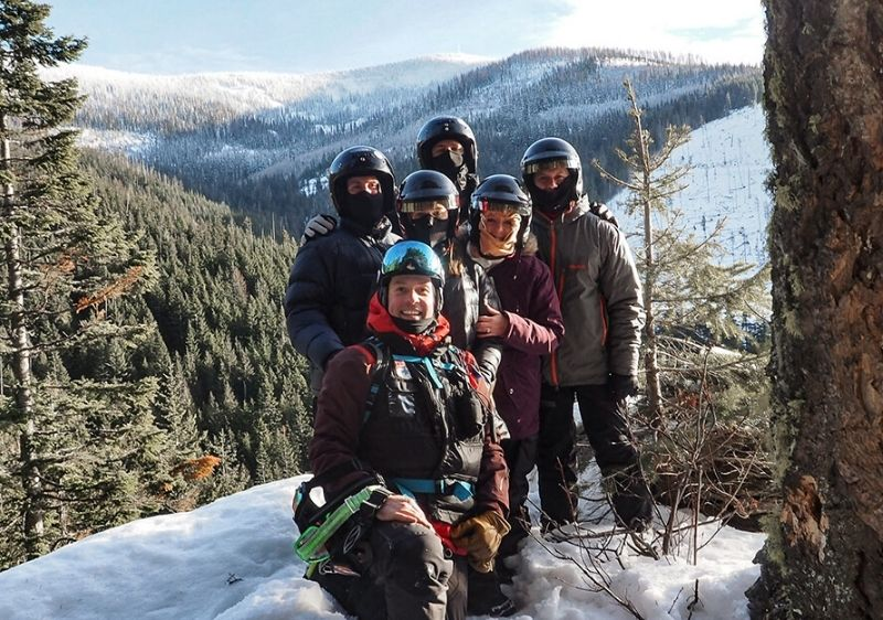 Snowmobiling-tour-group-poses-on-Priest-River-Valley-trail