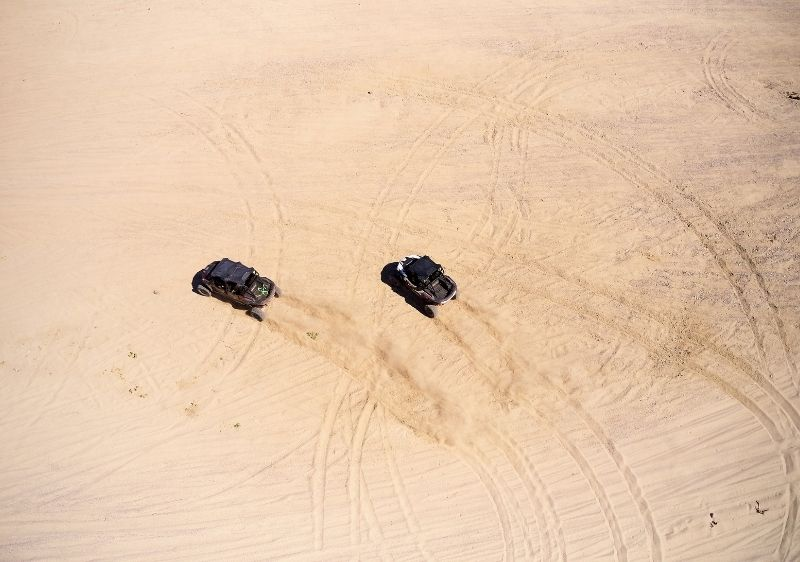 aerial view of off-road vehicle driving through sand