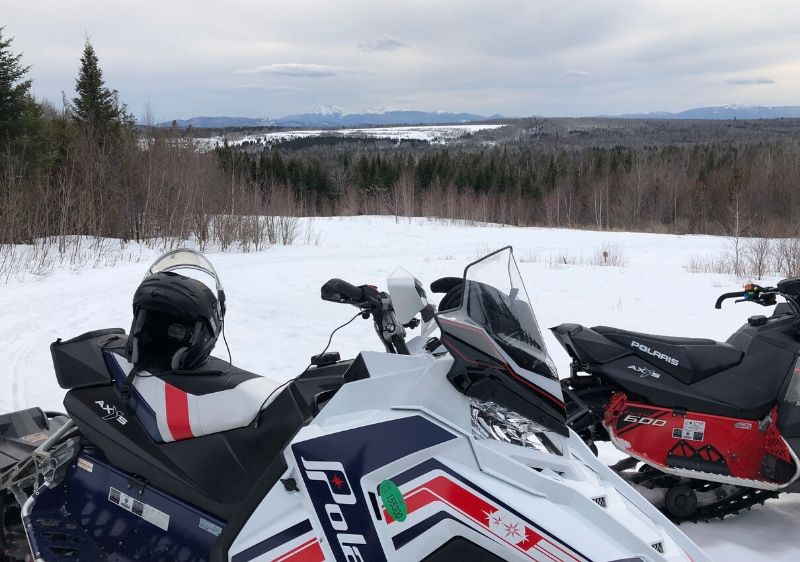 Polaris-Snowmobiles-parked-along-a-scenic-moutain-view