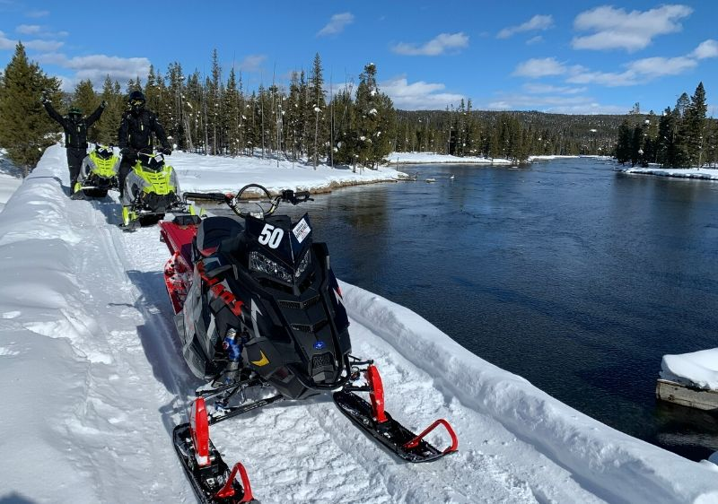 guests-on-Polaris-Snowmobiles-driving-along-an-open-lake