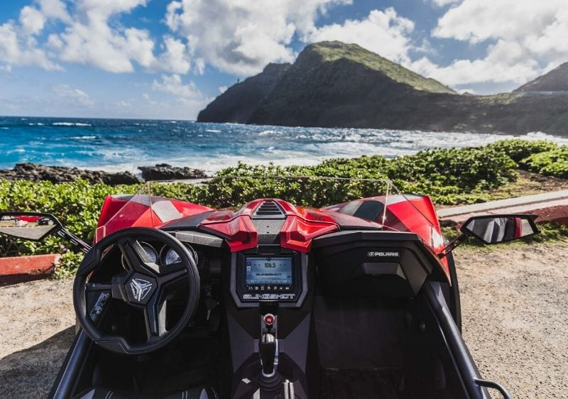 front seat of a Polaris Slingshot parked by the coast