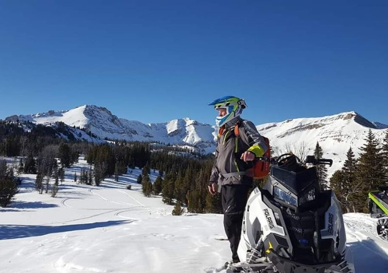 guest-standing-by-a-Polaris-snowmobile-overlooking-the-scenic-mountain-range