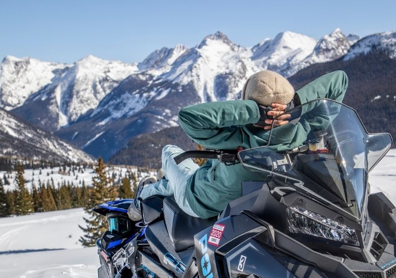 guest on snowmobile gazing at San Juan Mountain view