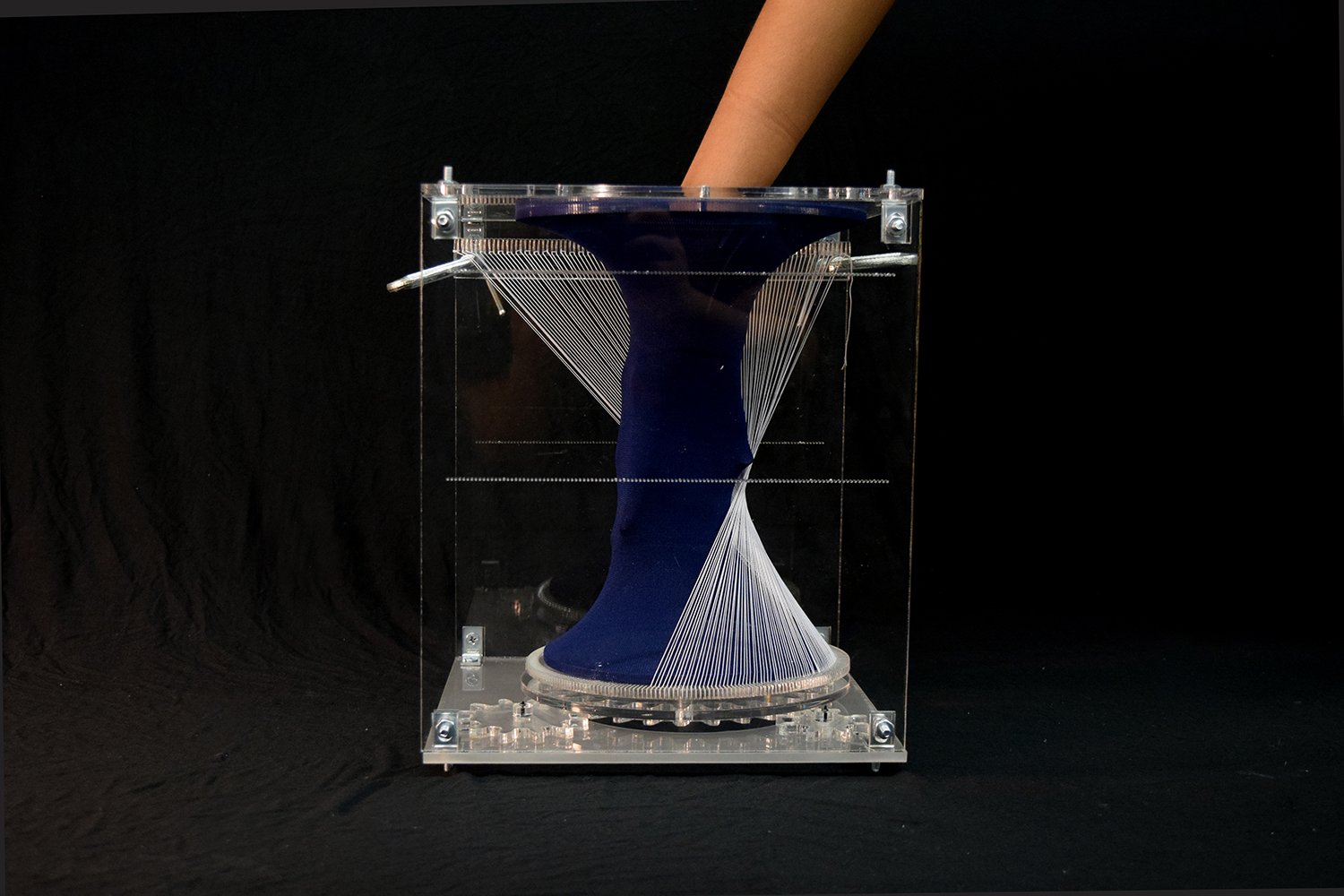 hand partially entering textile form through a hole in one face of the vertical acrylic box