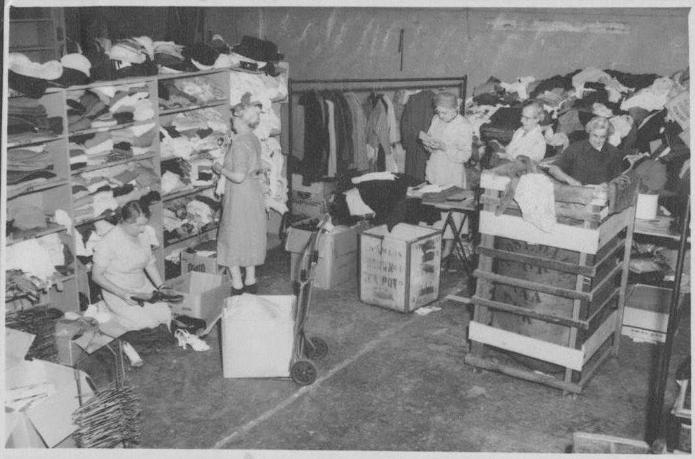 This is a black and white photo of a few female volunteers sorting clothes and other second-hand items in a warehouse facility.