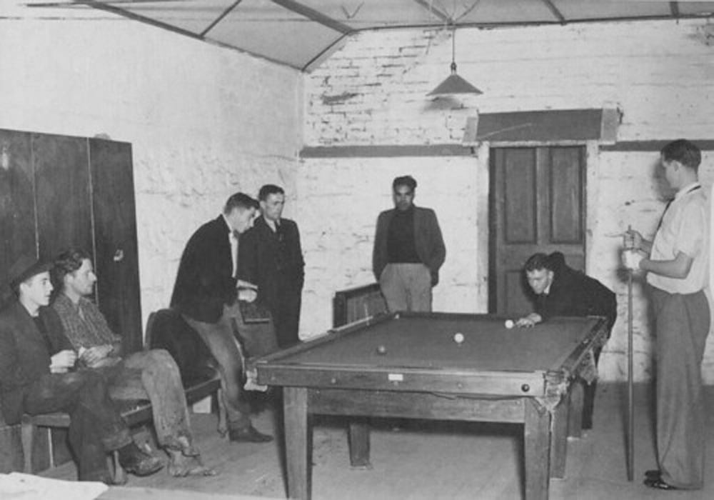 This black and white photograph is of seven young men playing billiards and sitting around the table in the club room at the boys hostel in Fitzroy.