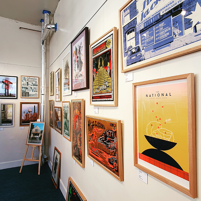 Fra,ed prints are displayed gallery-style against a white wall
