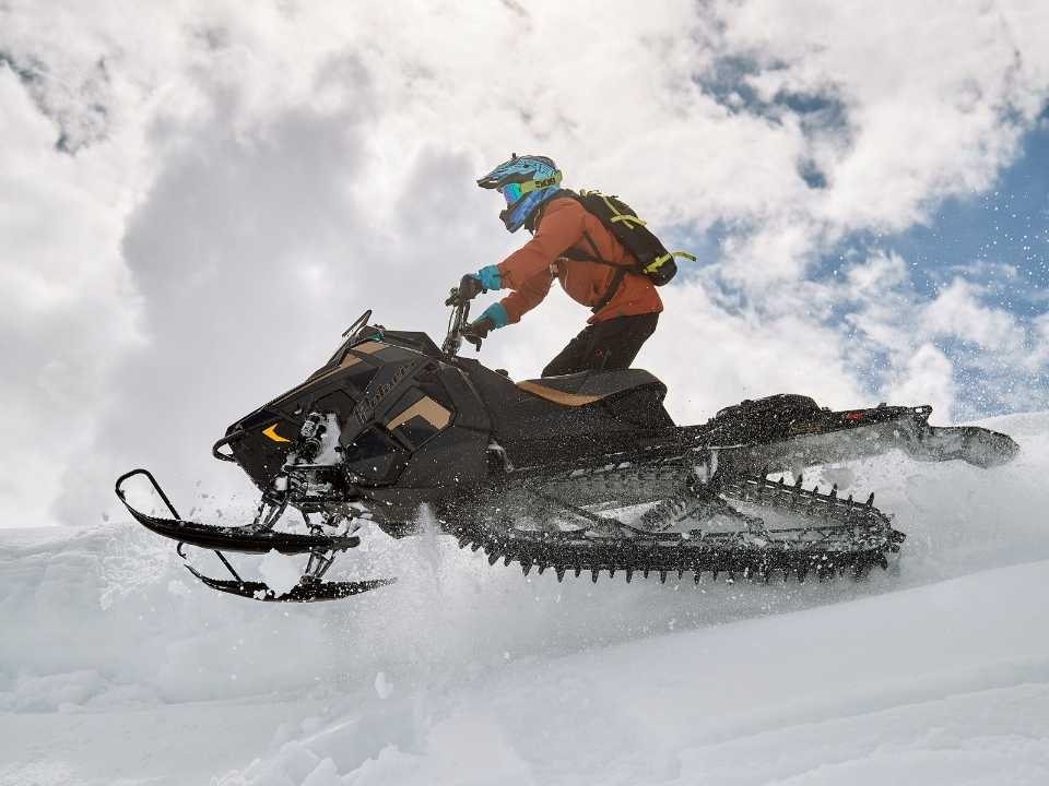 snowmobiler driving up a snow drift