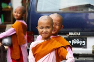 Young Buddhist Nuns smile wearing pink and orange