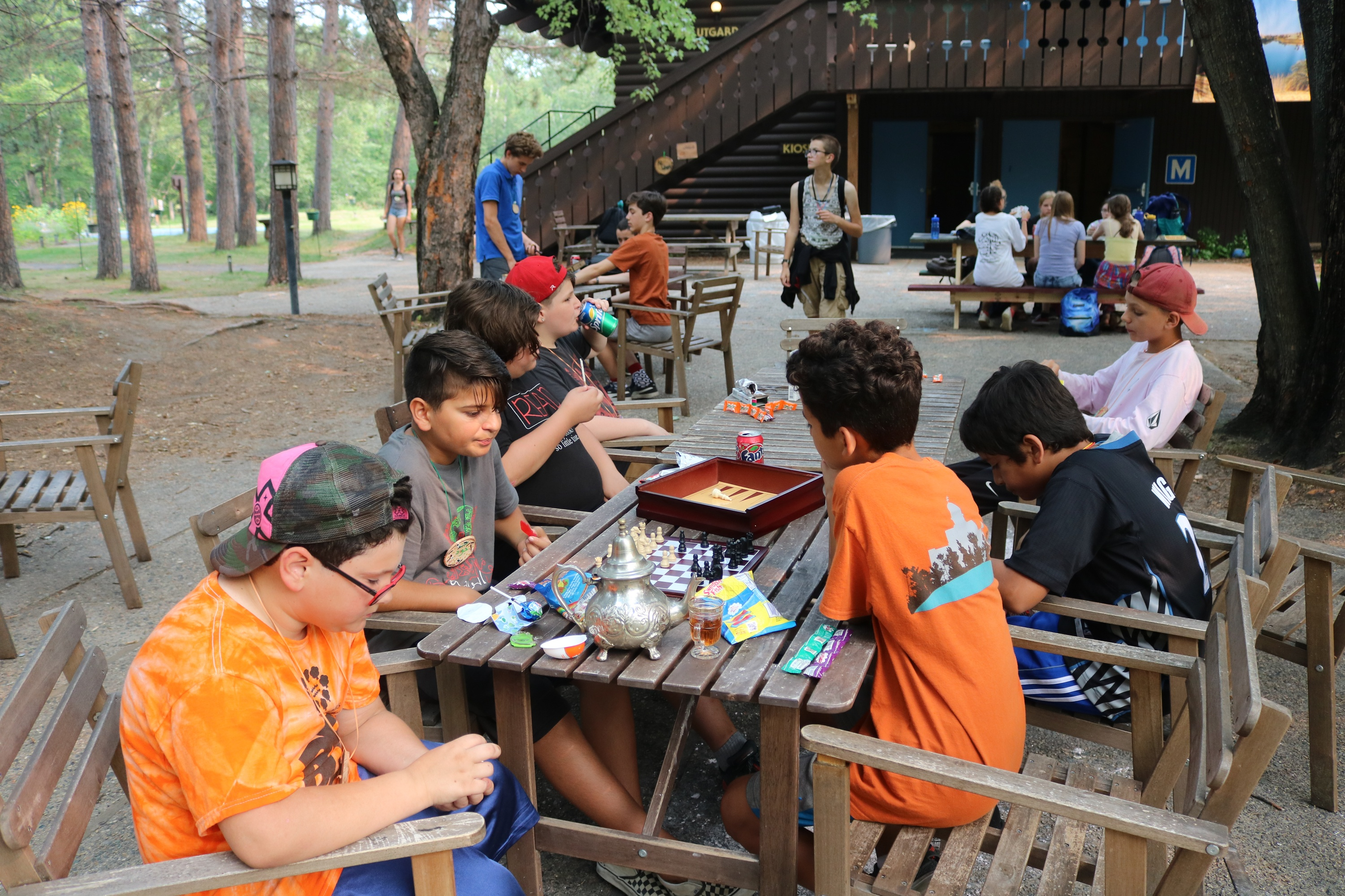 Villagers sitting at a table drinking mint tea and playing chess.